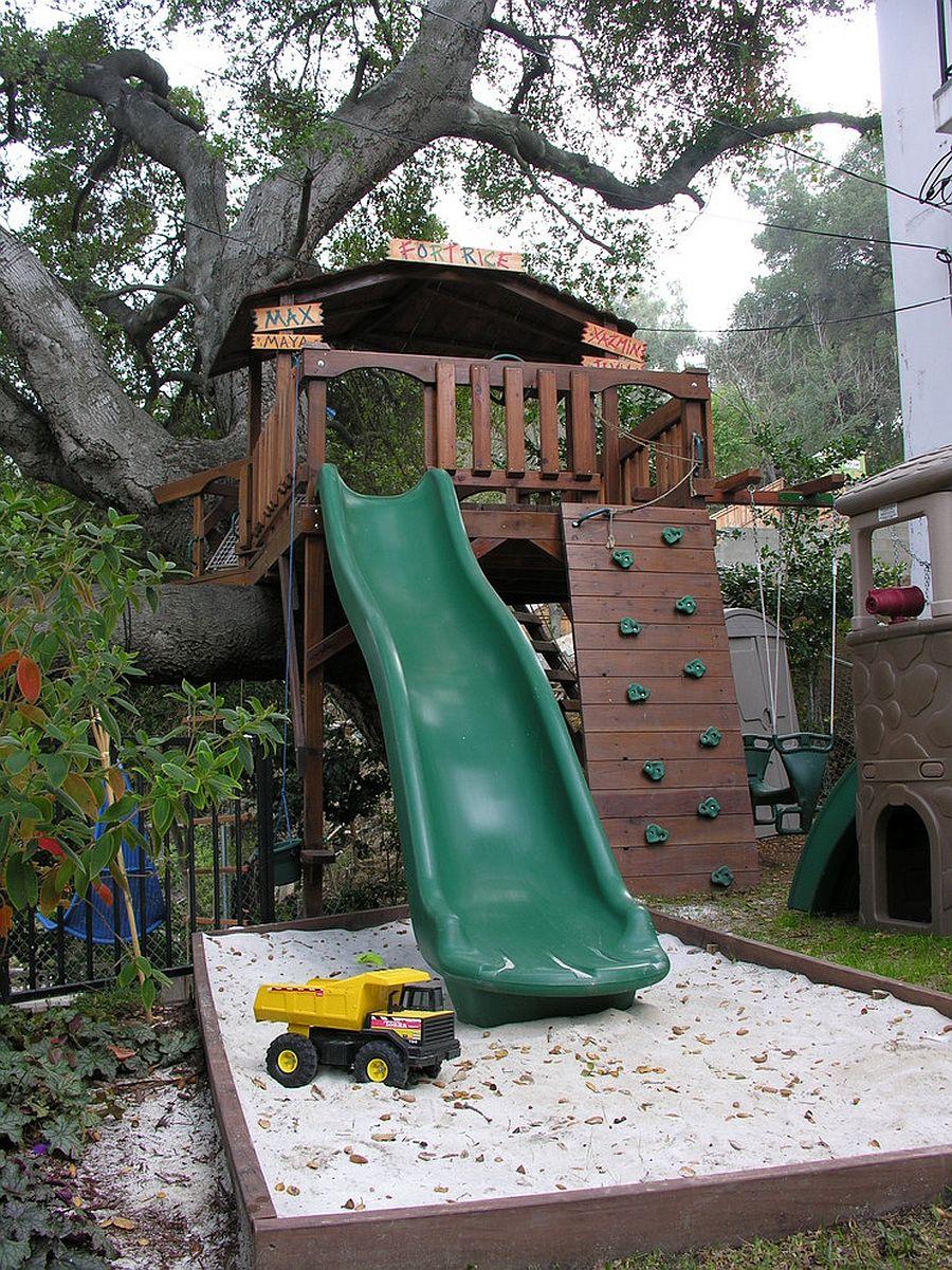 Treehouse built into an oak tree along with a slide and sandbox make for a dream backyard playarea