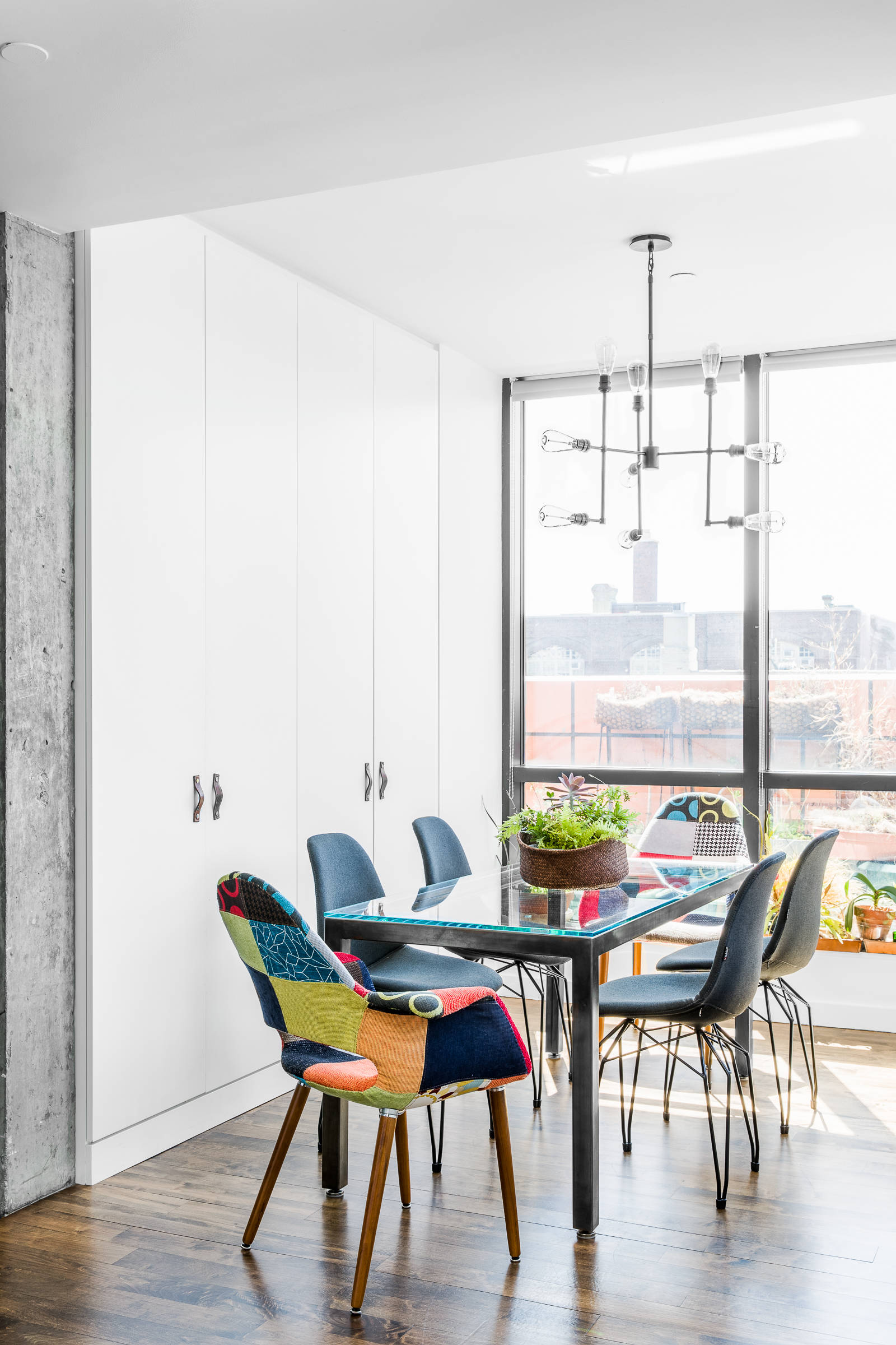 Two multi-colored chairs add contrast to this small contemporary dining room in neutral hues
