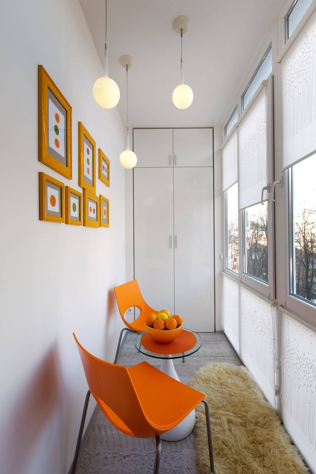 Wall art frames and chairs bring pops of orange to this small contemporary sunroom