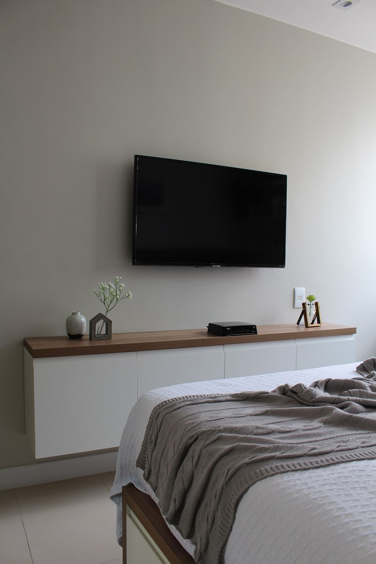 Wall-mounted TV in the bedroom along with a slim storage space below