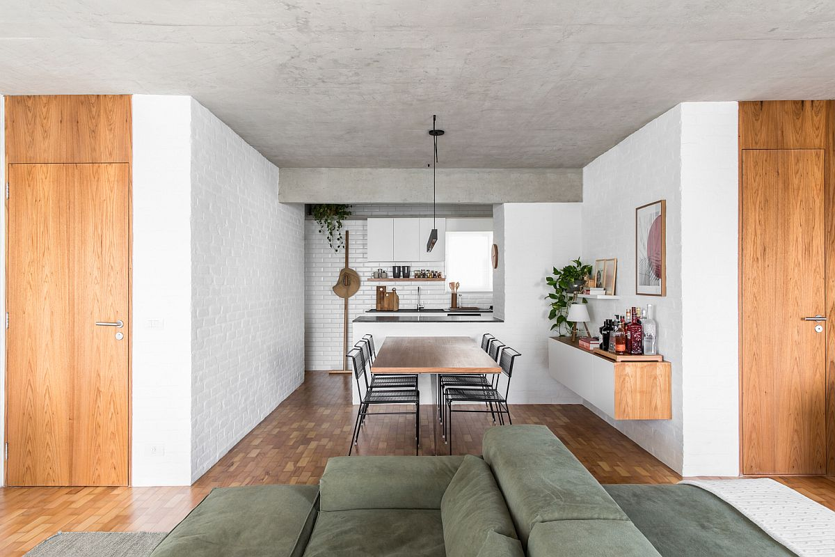 White subway tiled backdrop of the kitchen allows it to blend in with the white painted brick walls of the apartment