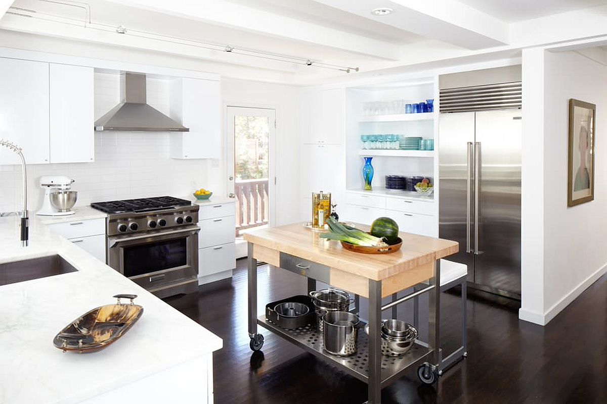 Wood and white kitchen with steel appliances and a lovely cart style island with steel base and wooden countertop