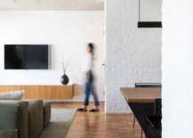 Wooden-floor-is-combined-with-rugged-concrete-ceiling-and-white-painted-brick-walls-inside-the-apartment-14089-217x155