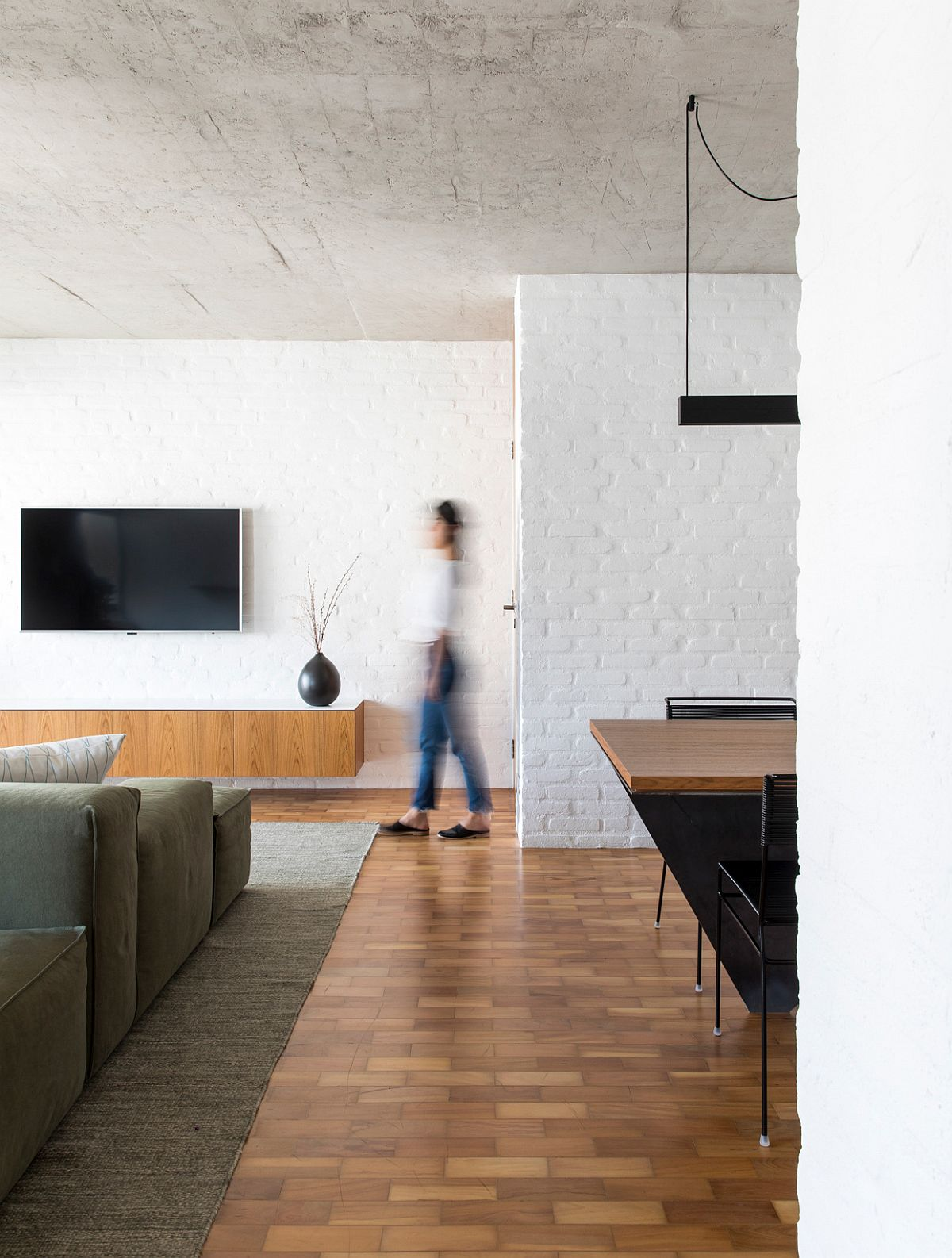 Wooden floor is combined with rugged concrete ceiling and white painted brick walls inside the apartment