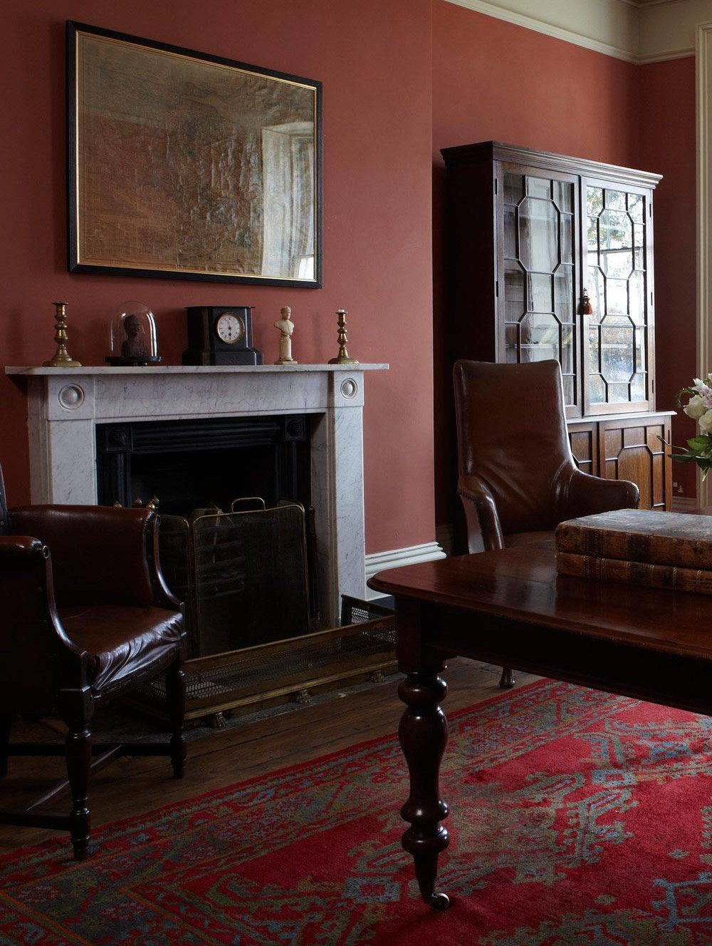 study with brown furniture, red wall and red carpet accent