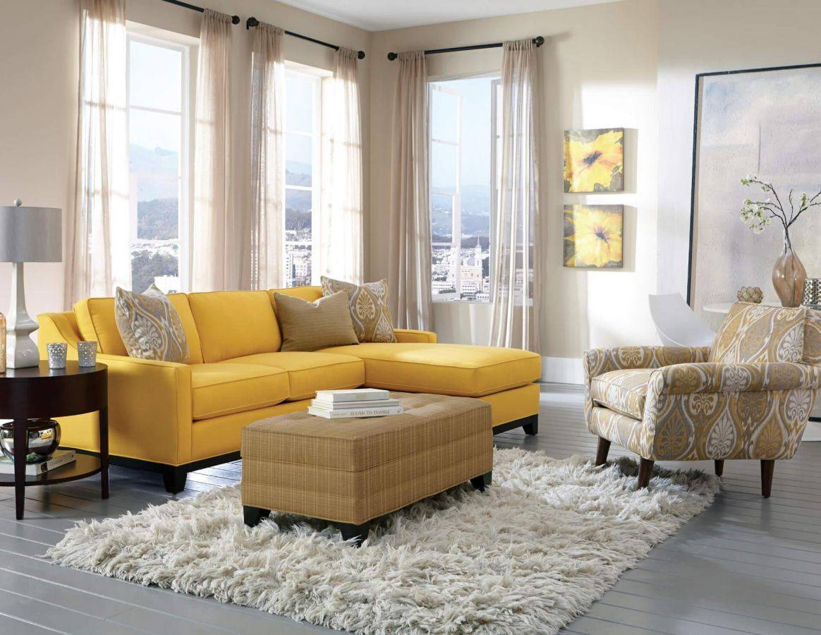yellow couch with brown chair and footstool in living room