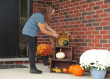 woman sets up fall porch display with wood crates and pumpkins