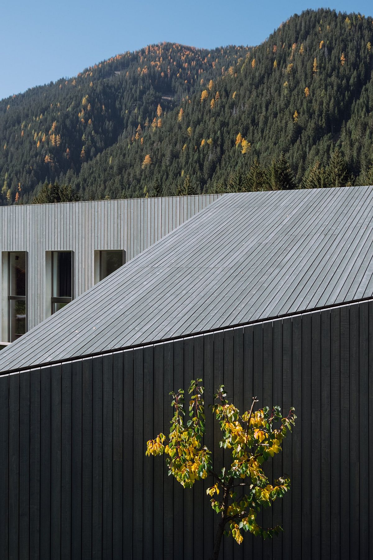 Angular walls and geometric style of the house stands in contrast to the picturesque natural backdrop