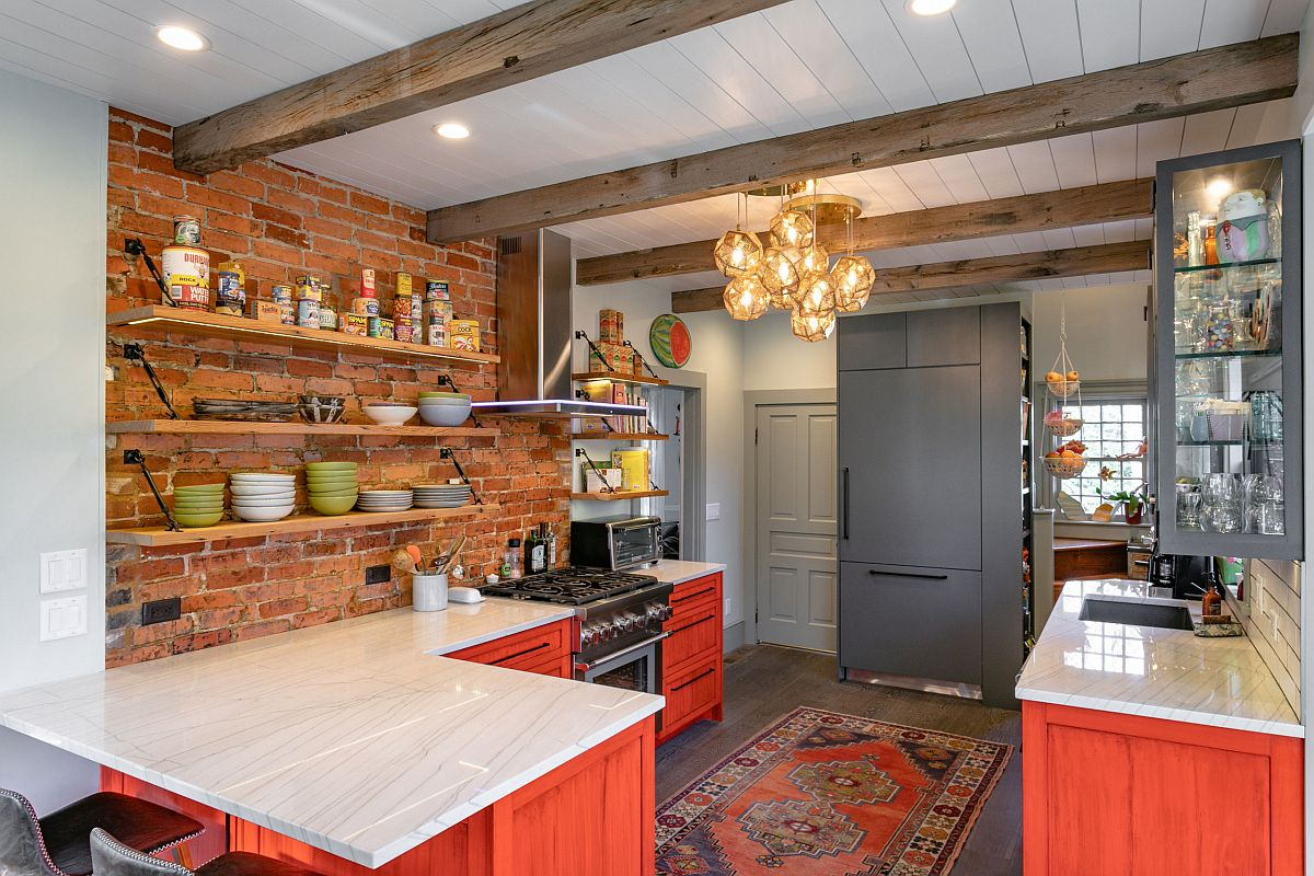 Beautiful farmhouse kitchen with exposed brick wall section and cabinets in brick red with an orangish tinge