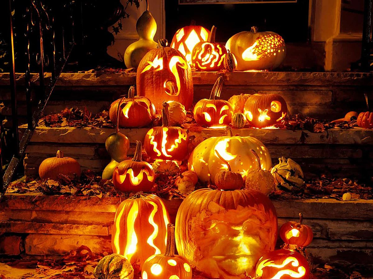 Carved pumpkins, Jack-o'-lanterns and fall leaves are combined to welcome you at this house