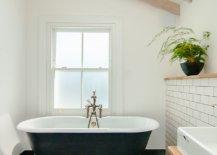 Clawfoot-bathtub-inside-the-renovated-modern-bathroom-in-white-and-black-46405-217x155