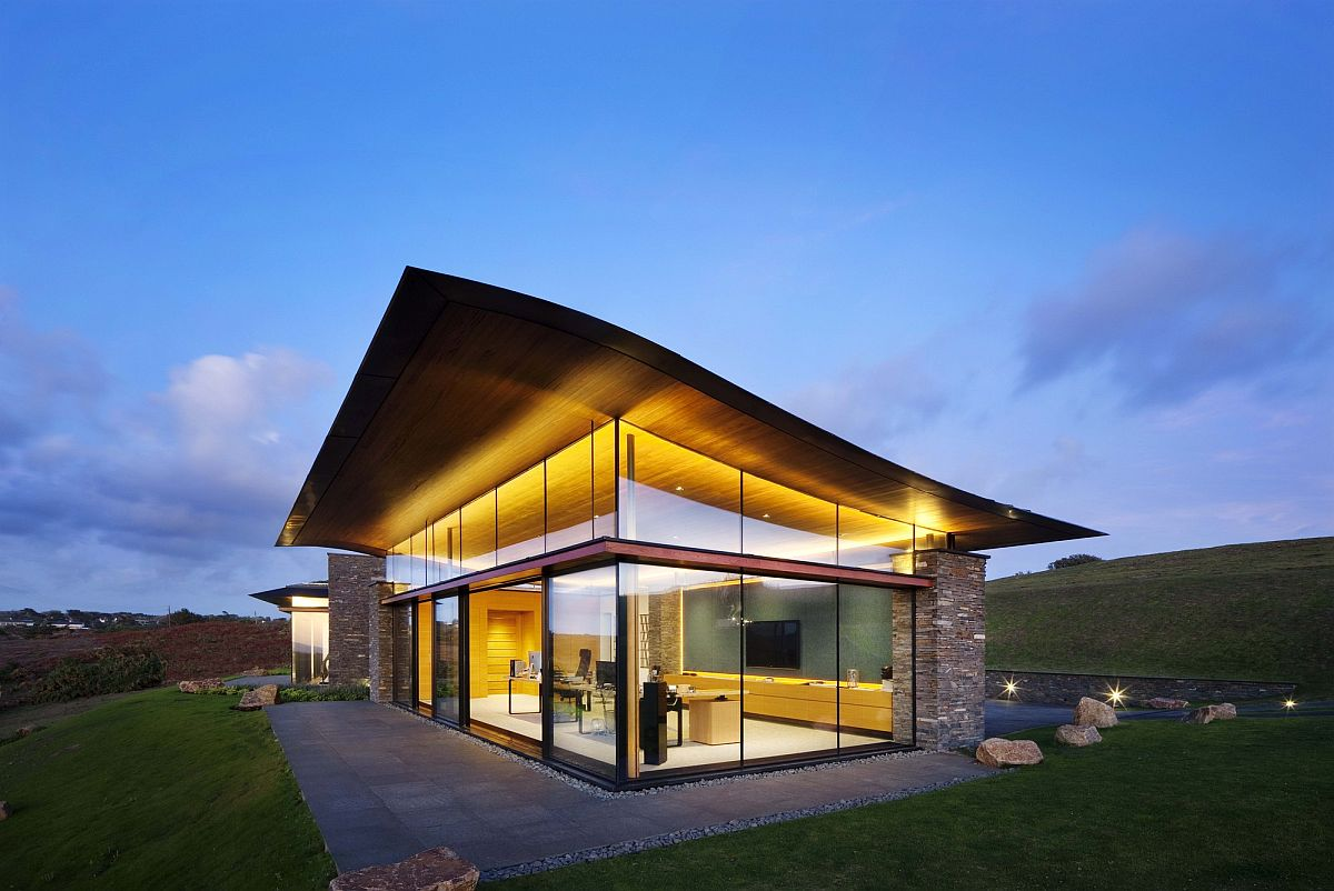 Curvy green roof, natural stone walls and floor-to-ceiling glass windows shape the Logie Point House