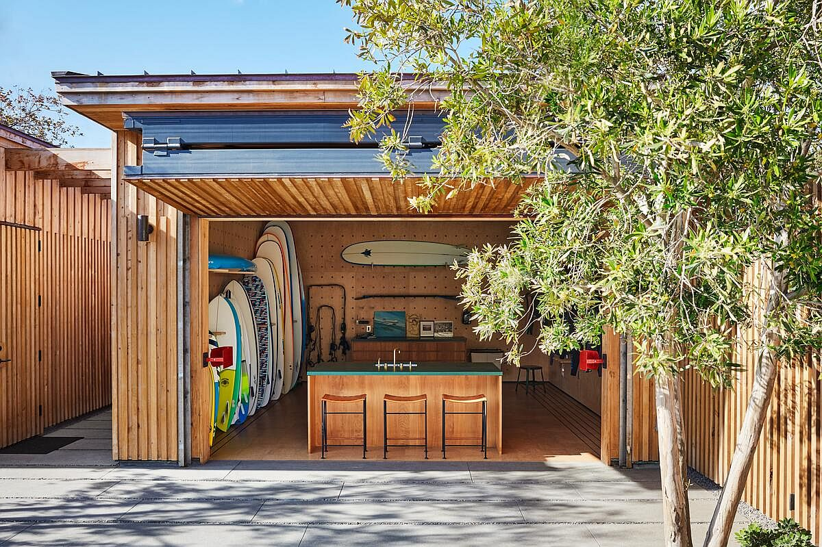 Customized surfboard storage unit at the entrance of the house acts as a windbreaker