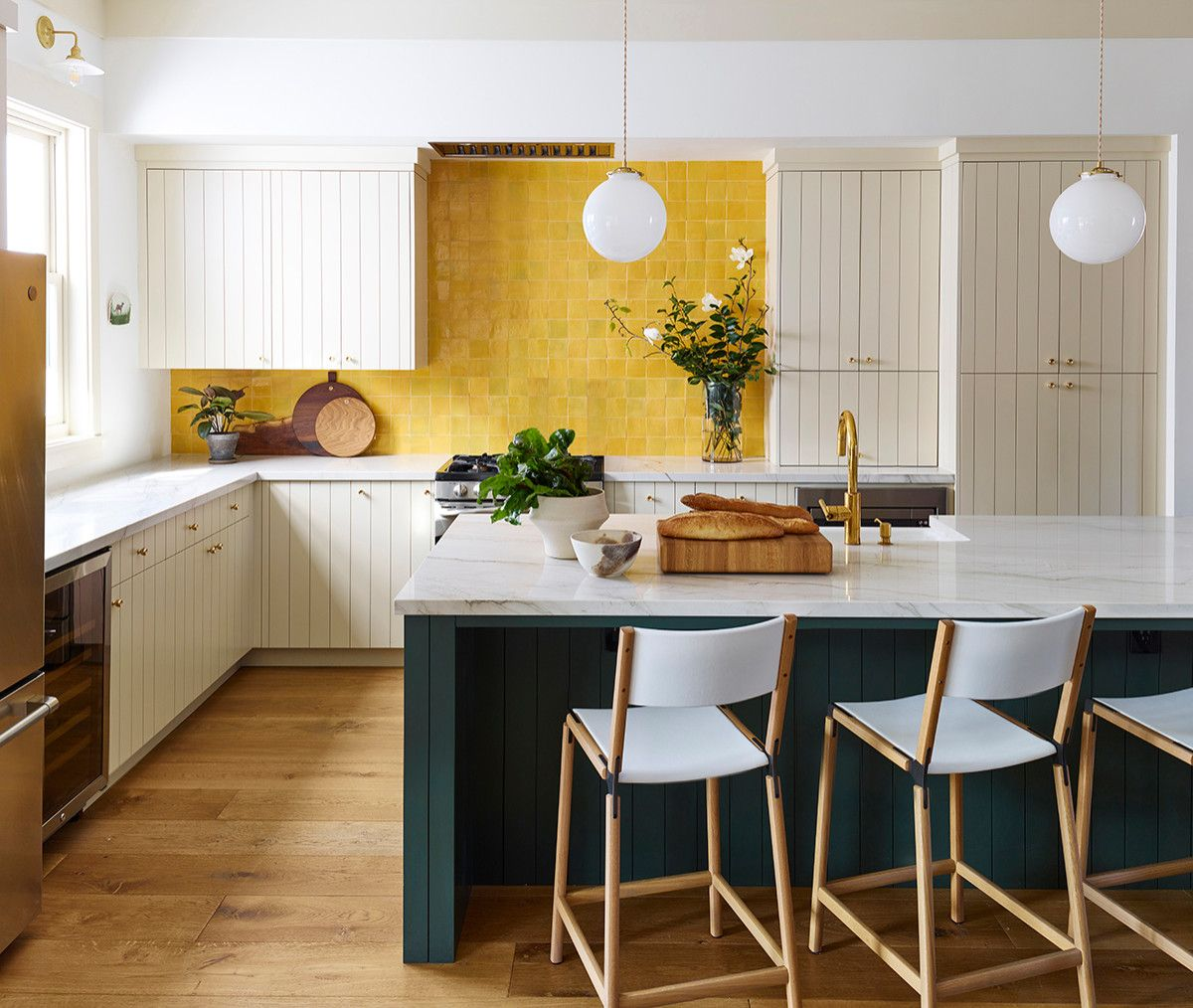 Dark green kitchen sialnd and a brilliant yellow backsplash for the chic farmhouse kitchen