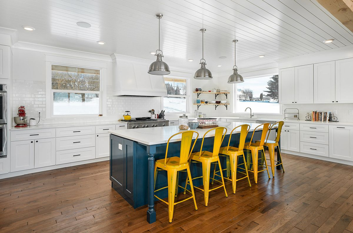 Dashing blue kitchen island coupled with dark yellow chairs makes a big visual impact in here