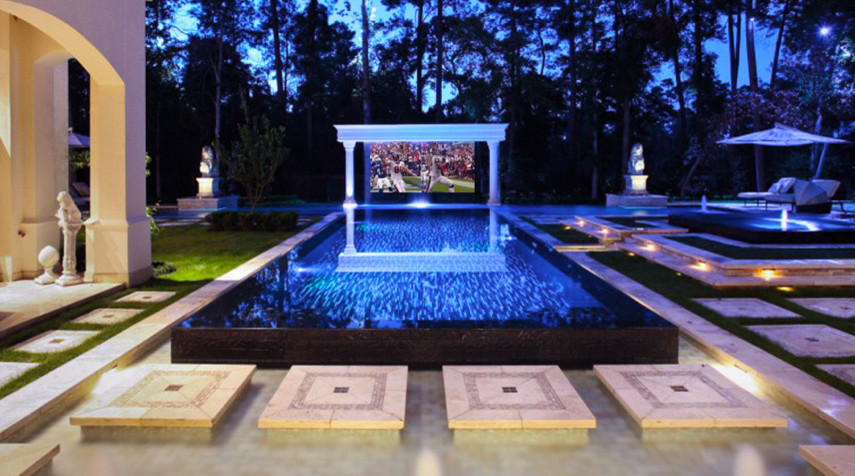 Drop-down screen and surround sound turn the pool deck into an outdoor home theatre
