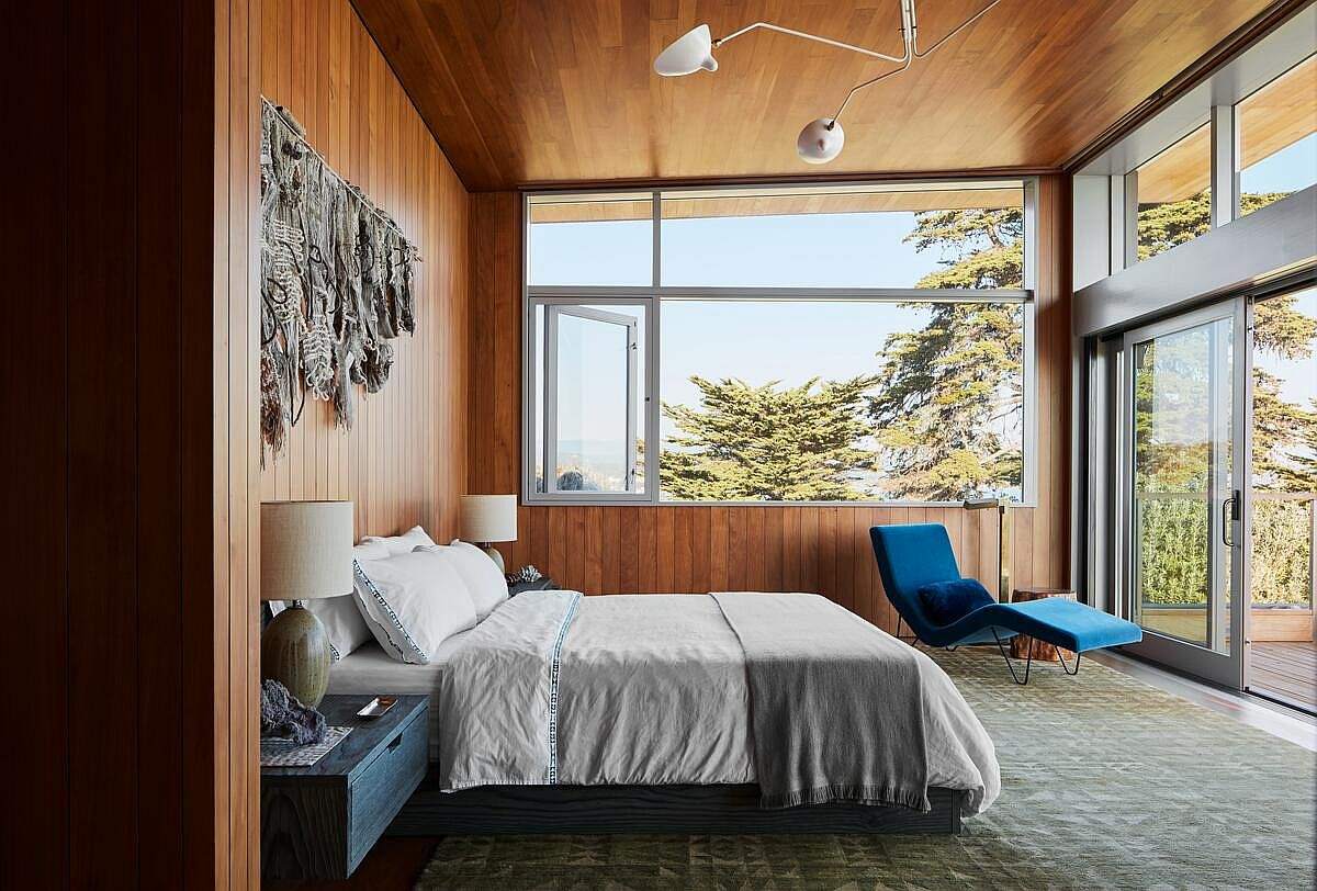 Gorgeous and cozy bedroom in wood with custom lighting is connected with the outdoors