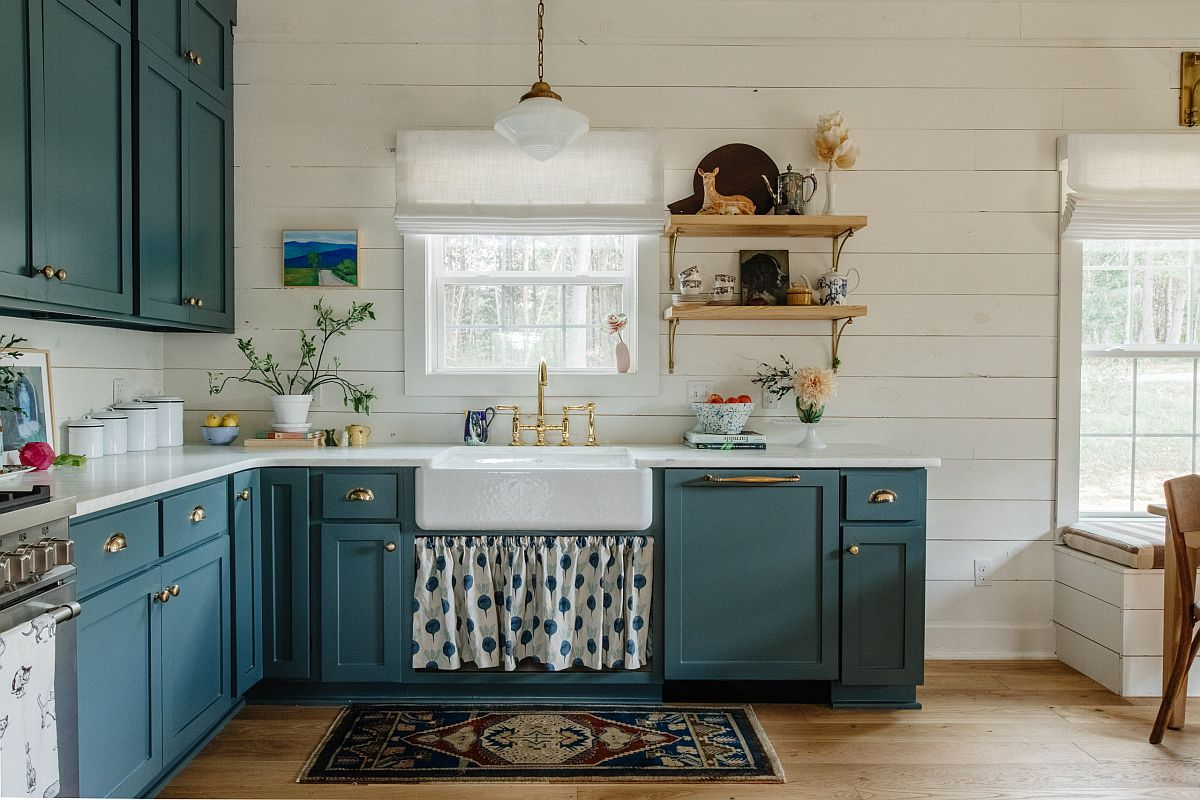 Gorgeous grayish blue cabinets along with brass handles bring bightness to this farmhouse style kitchen