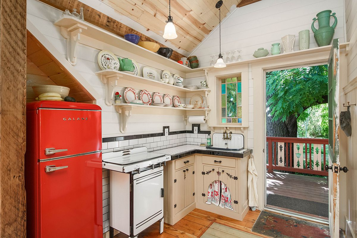 It is the vintage refigerator in red that brings color to this small farmhouse style kitchen in wood and white