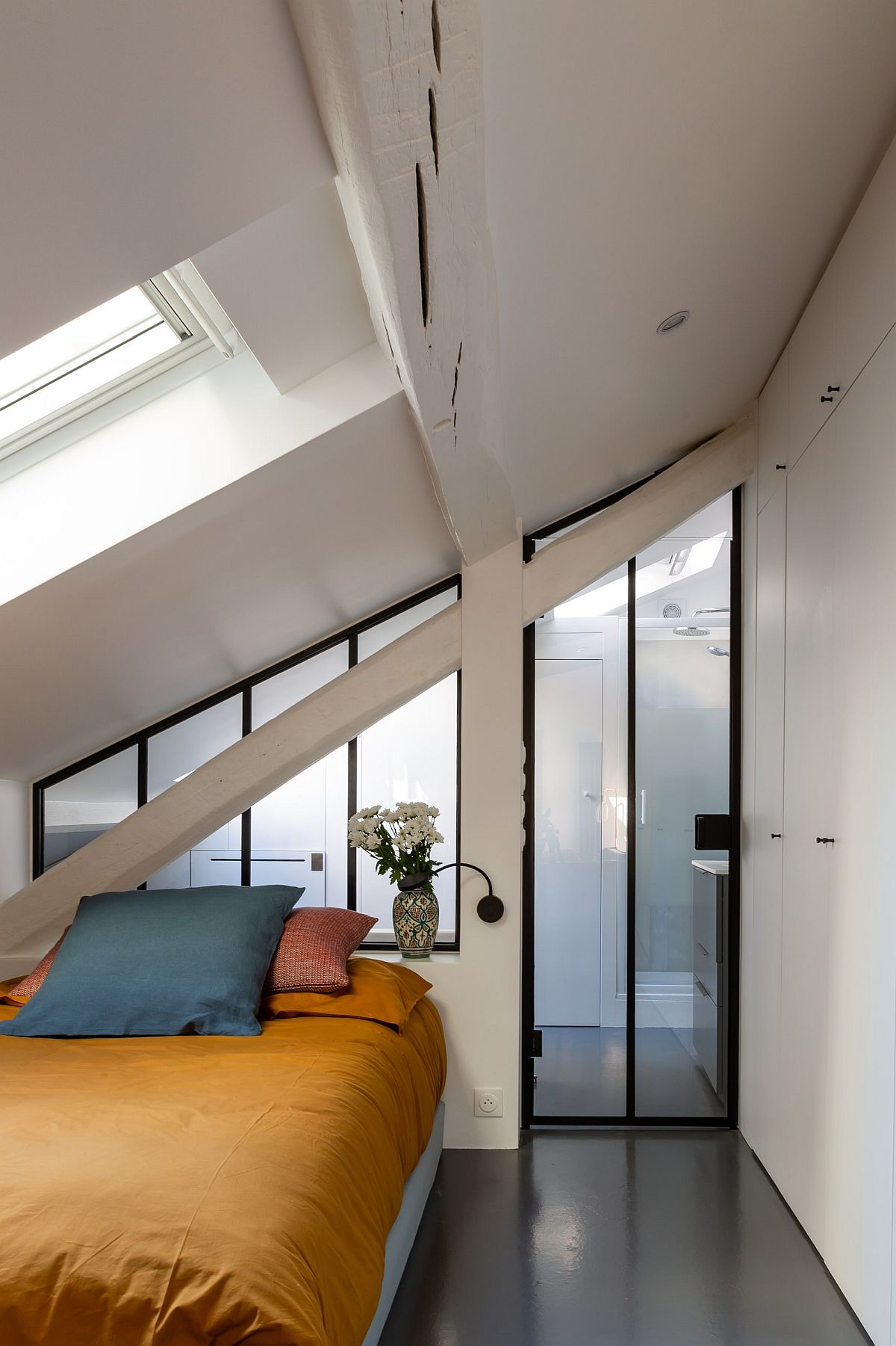 Light-filled-small-bedroom-of-French-apartment-with-white-walls-skylights-gray-floor-and-colorful-bedding-86475