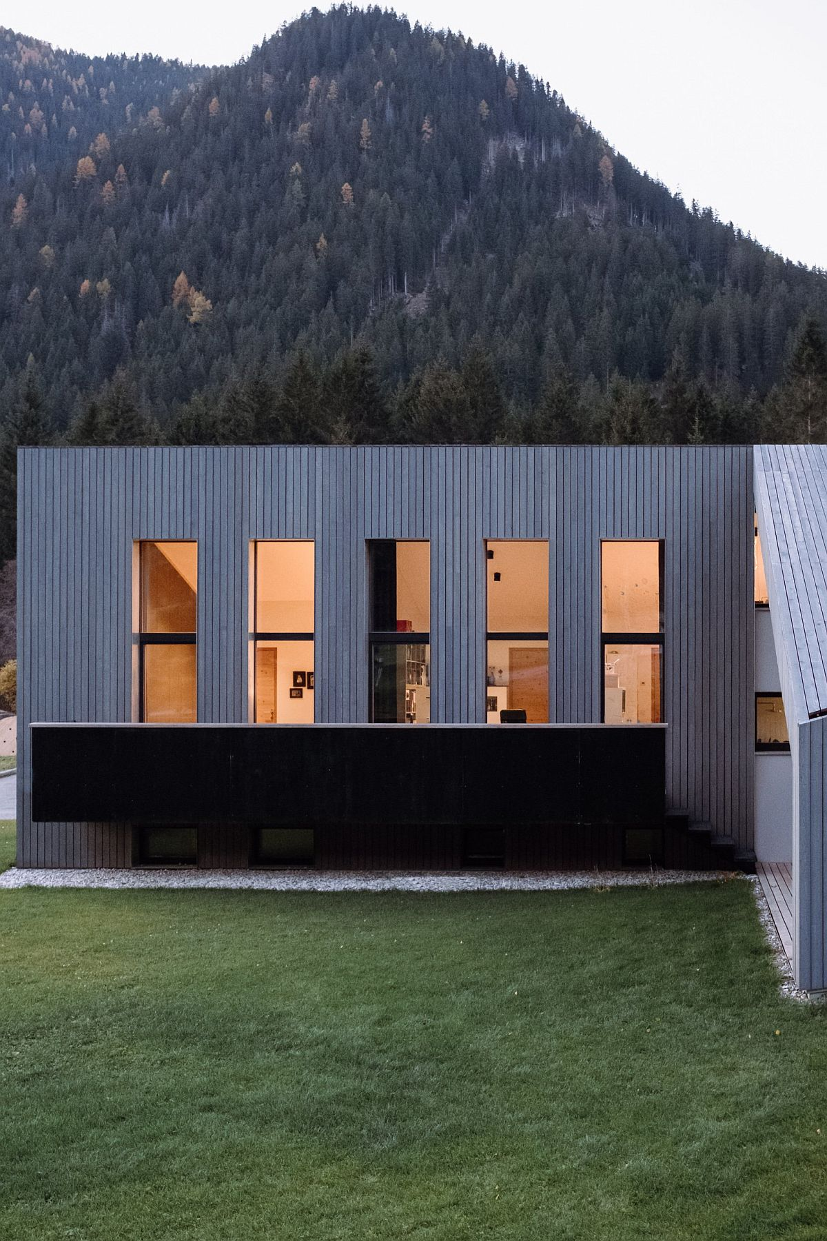Lovely protected forests and mountains shape the backdrop of the L-shaped house