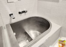Metallic-soaking-tub-is-integrated-with-the-bathroom-design-and-features-a-comfortable-space-to-sit-63931-217x155