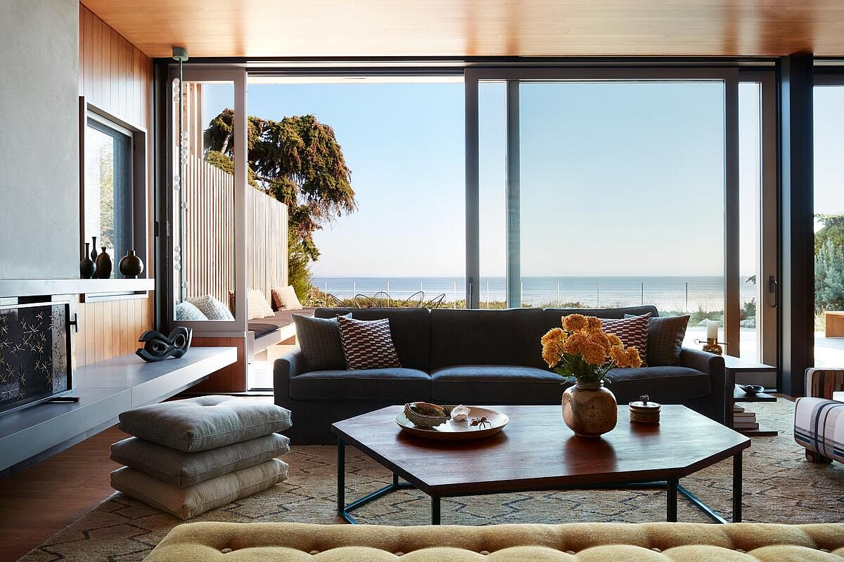 Modern beach style retreat in California with an open plan living space that is connected with the deck outside