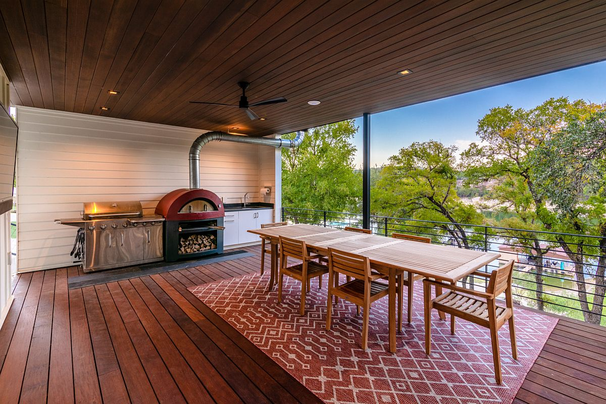 Modern farmhouse style deck with a lovely outdoor dining space, colorful area rug and barbecue zone