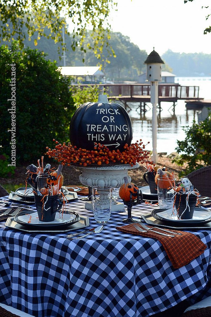 Outdoor Halloween table decorated beautifully with pumpkins in black and pops of orange