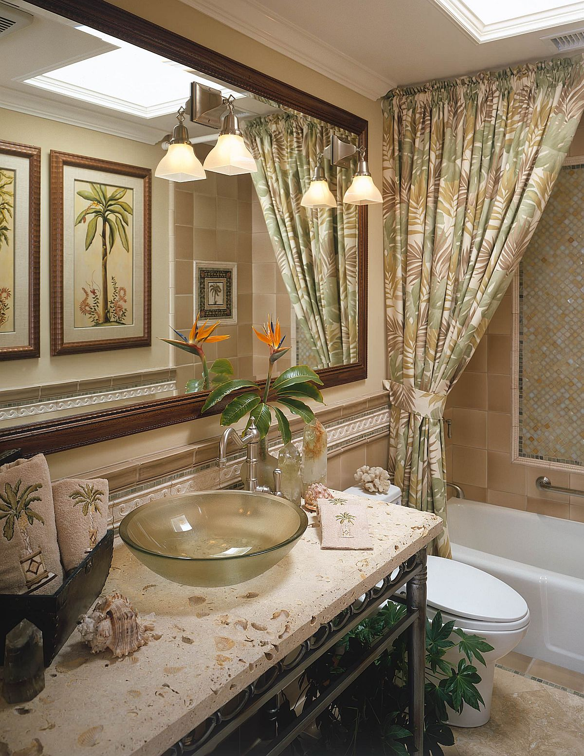 Pattern-filled tropical style bathroom in green with lovely sconce lights