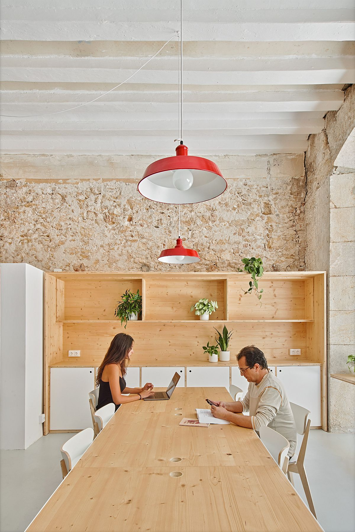 Pendant lights in red add color to the fabulous interior in brick white