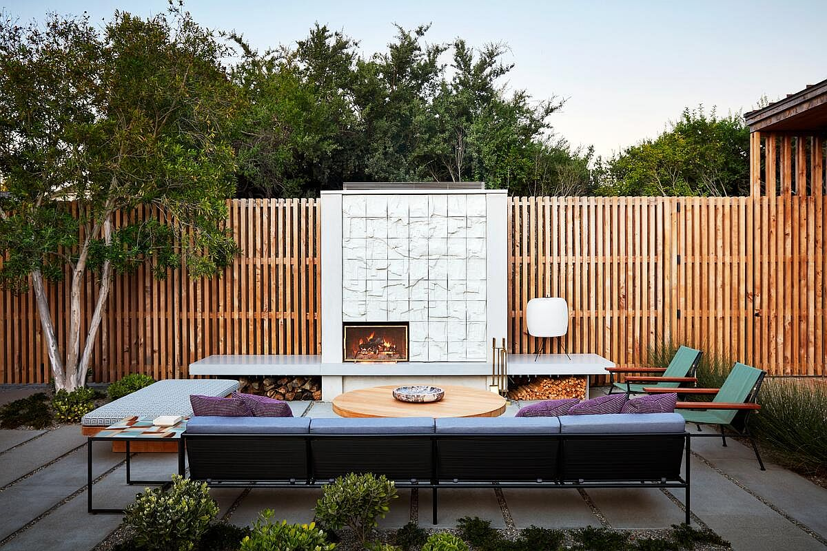 Relaxing rear yard hangout next to the fireplace is surrounded by wooden fence