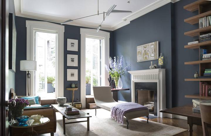 blue living room walls with high ceiling and brown furniture