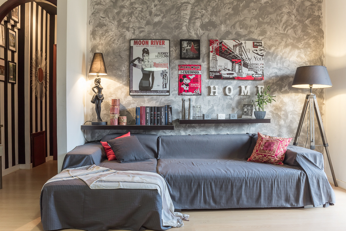 Small eclectic living room with a textured wall in the backdrop and a small couch in gray