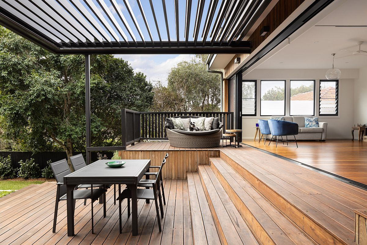 Spacious wooden deck of the contemporary home feels like a natural extension of the interior