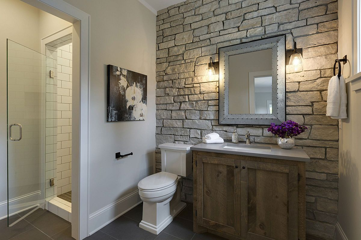Stone wall in the modern farmhouse bathroom steals the show instantly
