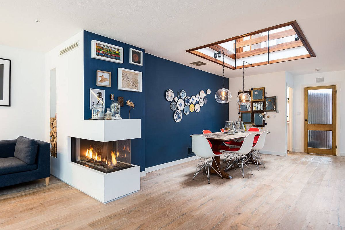 Delightful blue accent wall, skylight and a double-sided fireplace brighten this dining room