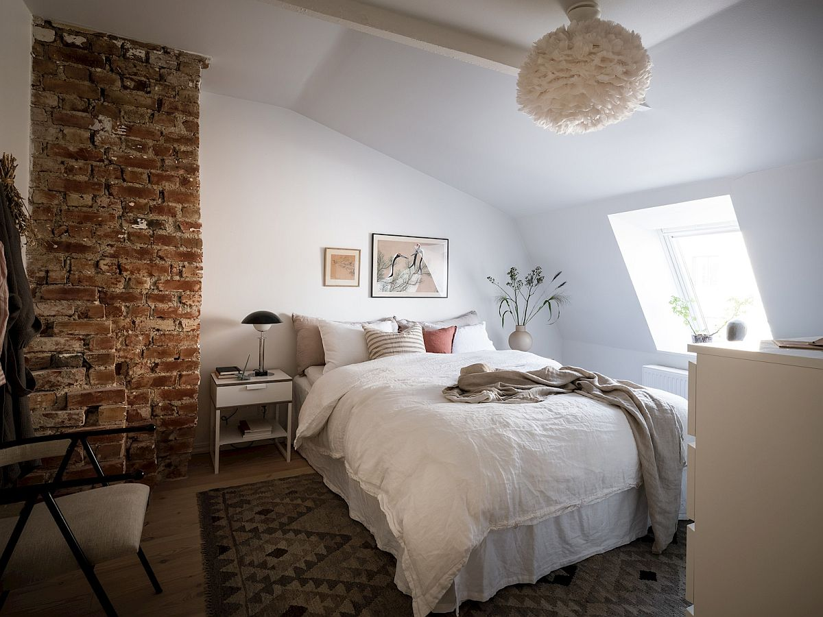 Exposed brick wall section brings an interesting visual and adds contrast to the small bedroom