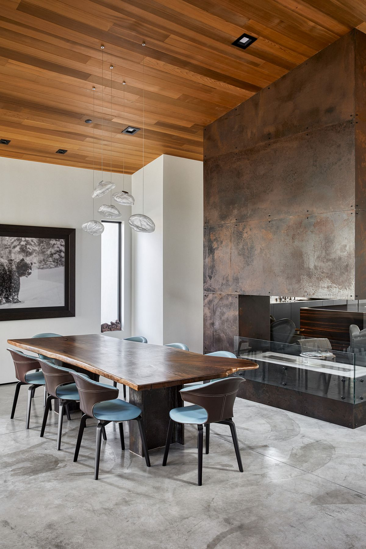 Exquisite dining room with double-sided fireplace that features a metallic wall