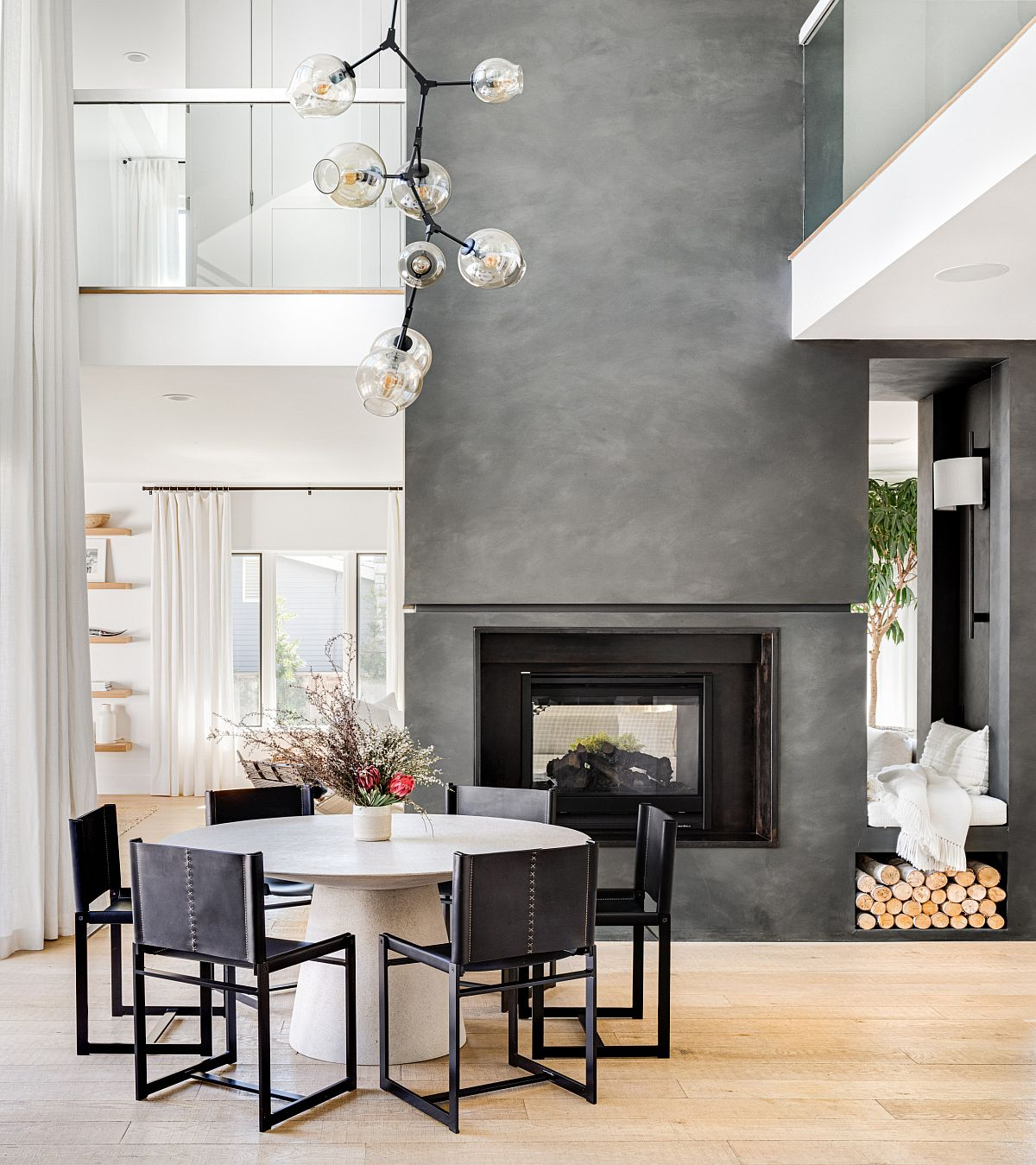 Fabulous fireplace in gray cement becomes the focal point of this amazing dining space