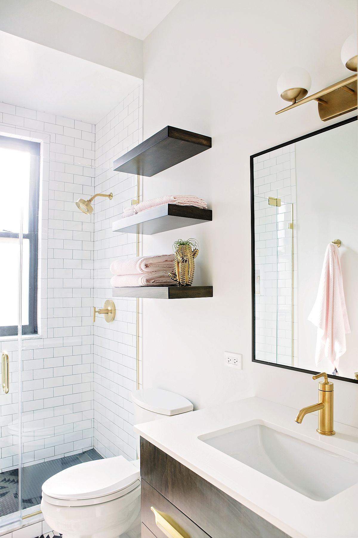 Guest bathroom in white with pops of black and gold tha bring contrast