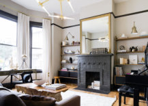 a brick fireplace painted black with mirror on mantel