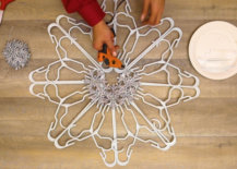 using hot glue gun and silver snowflakes to decorate hanger