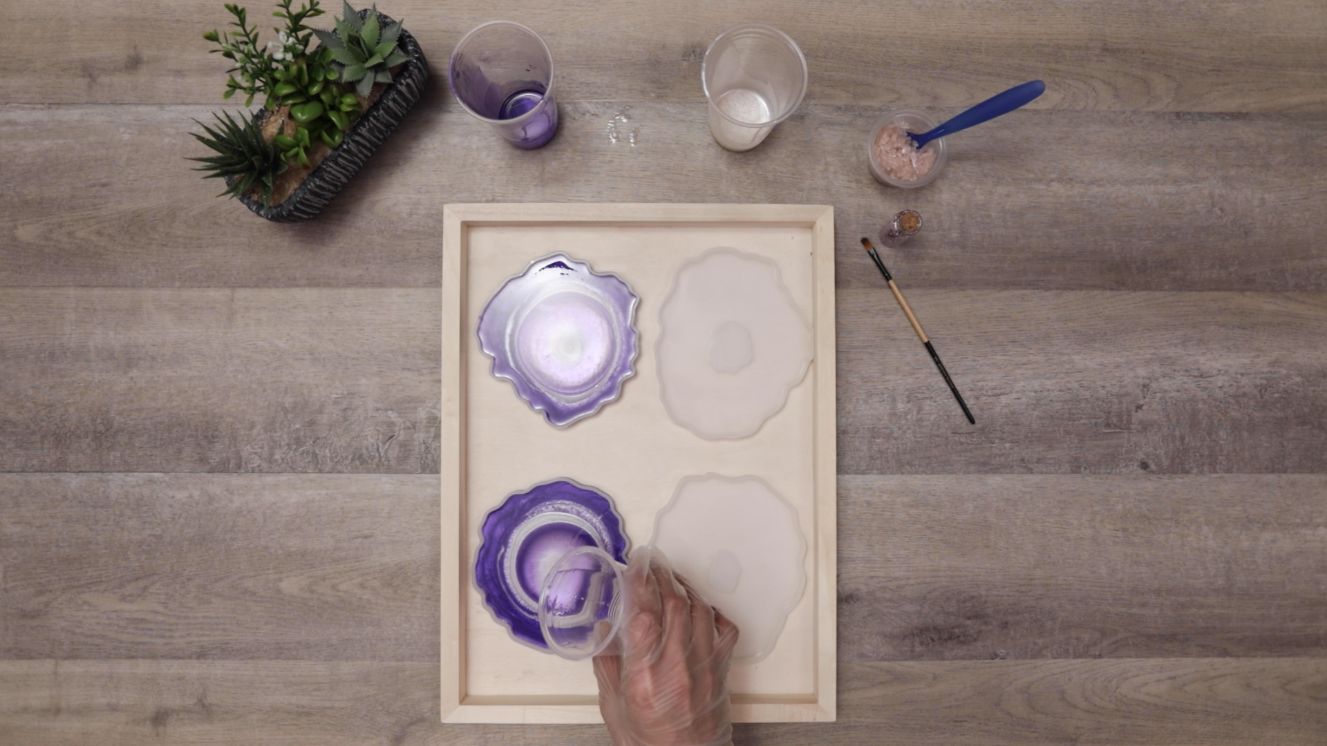 pouring clear resin into center of coasters to push color out
