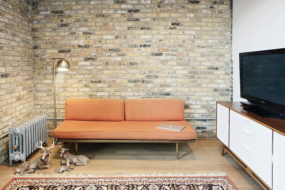 Small, upper level sitting space and living area of the home with an exposed brick wall