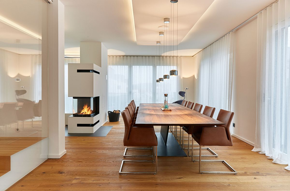 Smart two-sided fireplace becomes the focal point in this all-white modern dining room