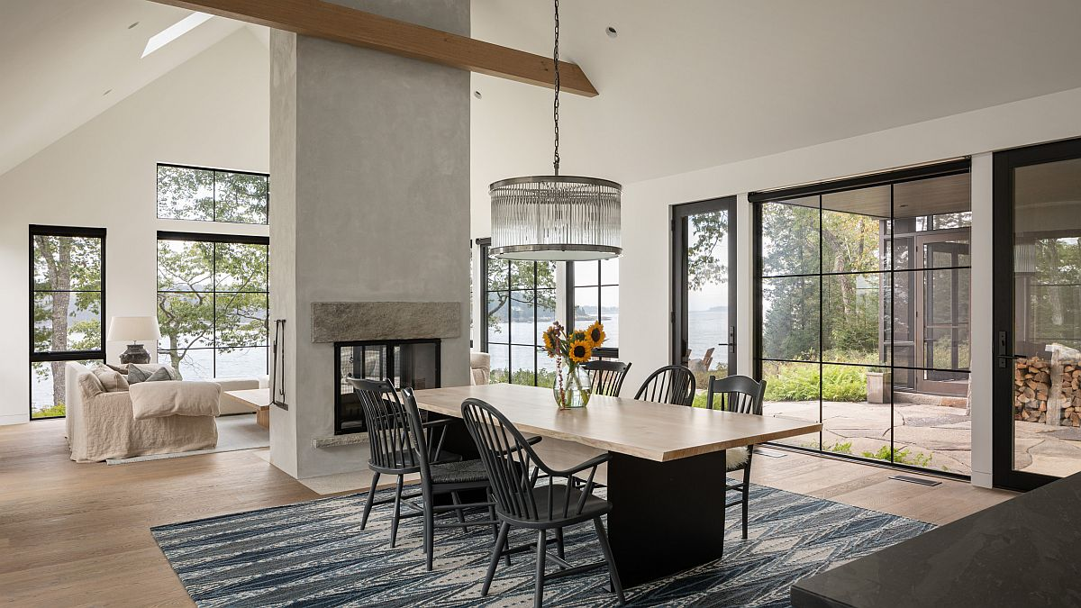 Spacious and elegant beach style dining room with lovely ambiance and a double-sided fireplace