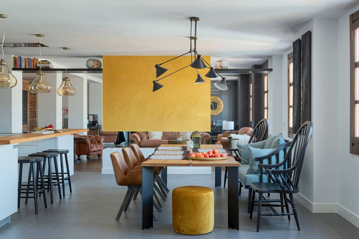 Vibrant yellow fireplace wall brings accent color to this dining room