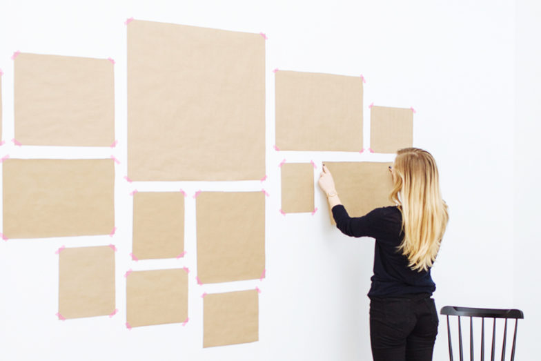 woman putting up templates for gallery wall
