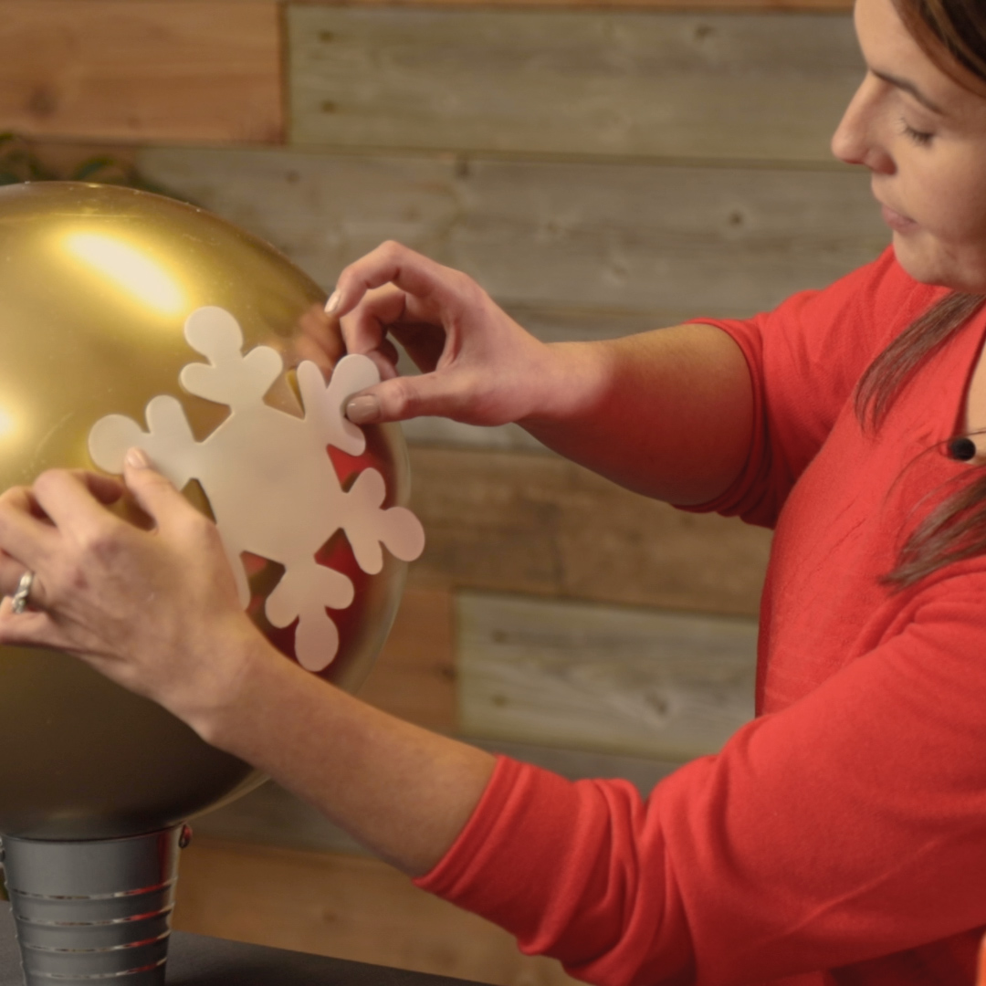 placing snowflake decal on gold ornament ball